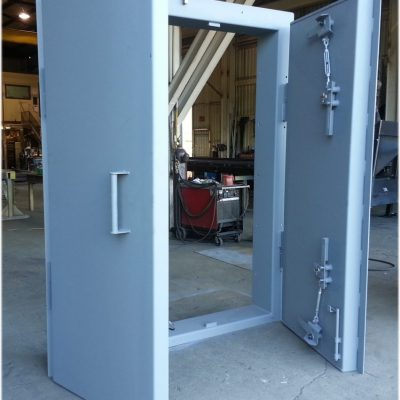 Double leaf door with deadbolt cam latches